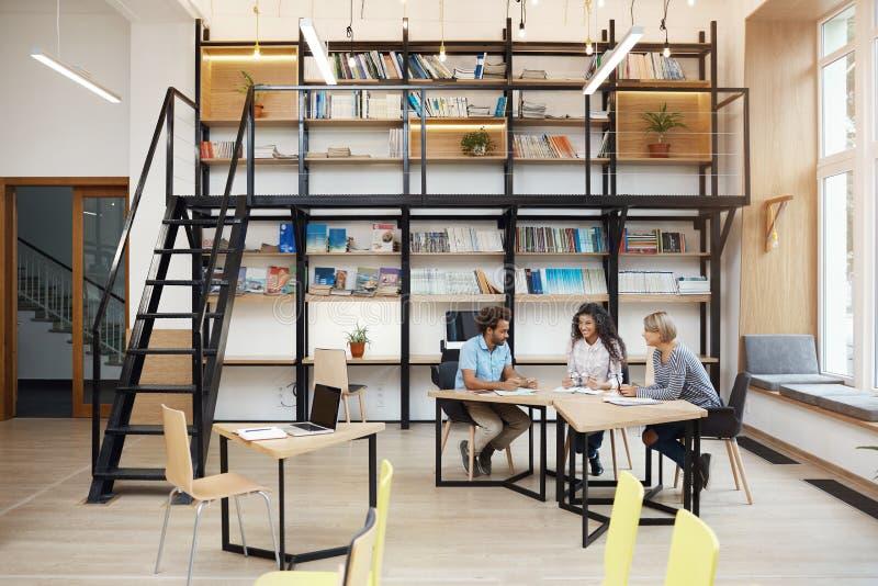 Группа в составе деловые партнеры на встрече обсуждая компанию приносит пользу, делающ исследование, смотря через работу ` s ompe стоковые изображения