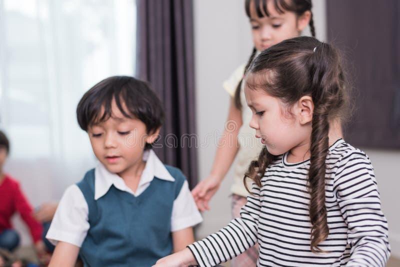Группа в составе дети играя совместно и иметь конфликт об игрушке в доме Маленькая девочка сердитая к мальчику Концепция образова стоковое фото