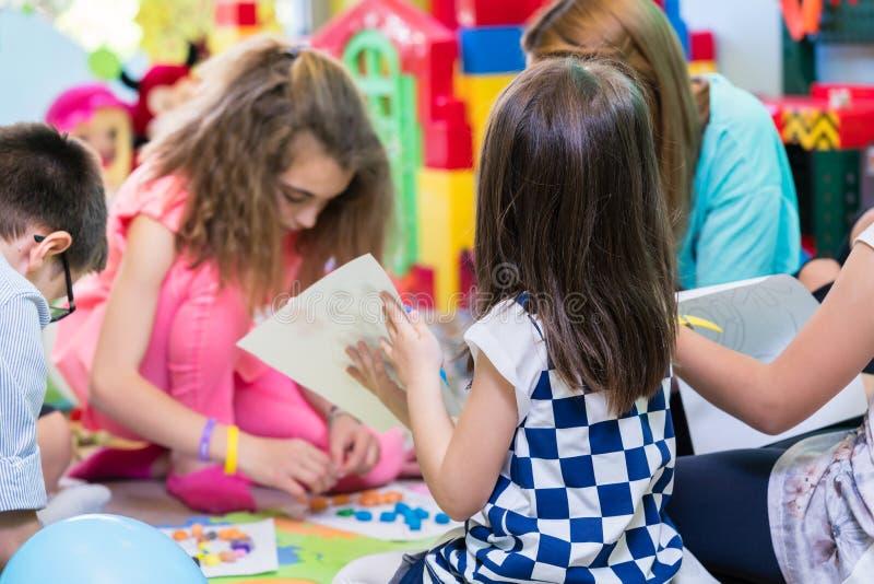 Группа в составе дети прикладывая красочный пластилин во время образовательной деятельности стоковые изображения