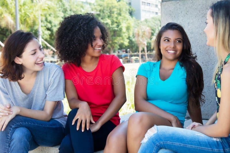 Группа в составе довольно женские молодые взрослые говоря outdoors стоковая фотография rf