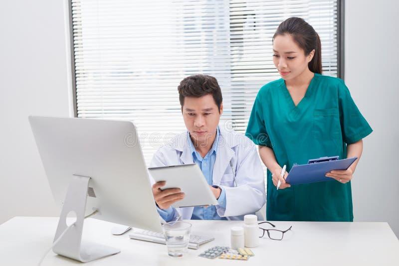 Группа в составе доктора и медсестры рассматривая медицинское заключение пациента Команда докторов работая совместно на пациентах стоковая фотография