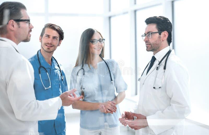 Группа в составе доктора обсуждая проблемы в коридоре больницы стоковое фото rf