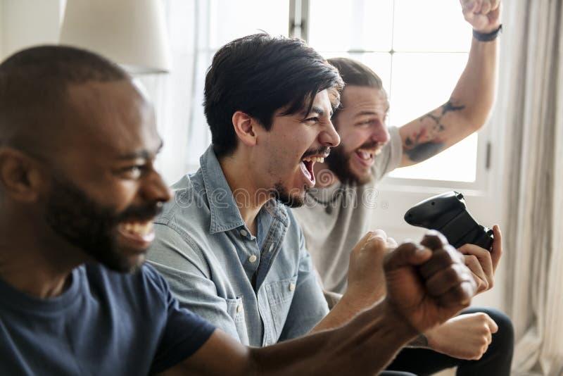 Группа в составе друзья играя видеоигры стоковое фото