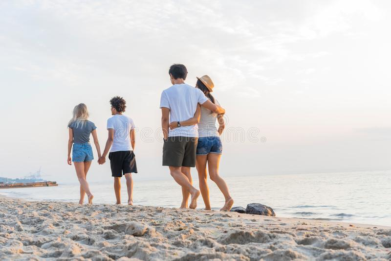 Группа в составе друзья идя вдоль пляжа на летнем времени Счастливое молодые люди наслаждаясь днем на пляже стоковая фотография