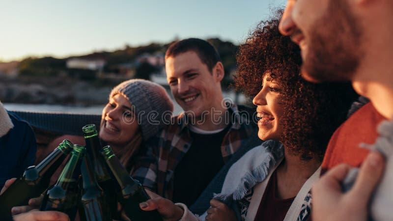 Группа в составе друзья имея партию на пляже стоковые изображения