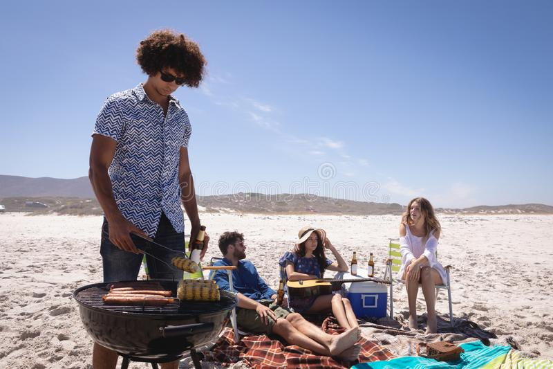 Группа в составе друзья имея потеху на пляже в солнечности стоковое изображение rf