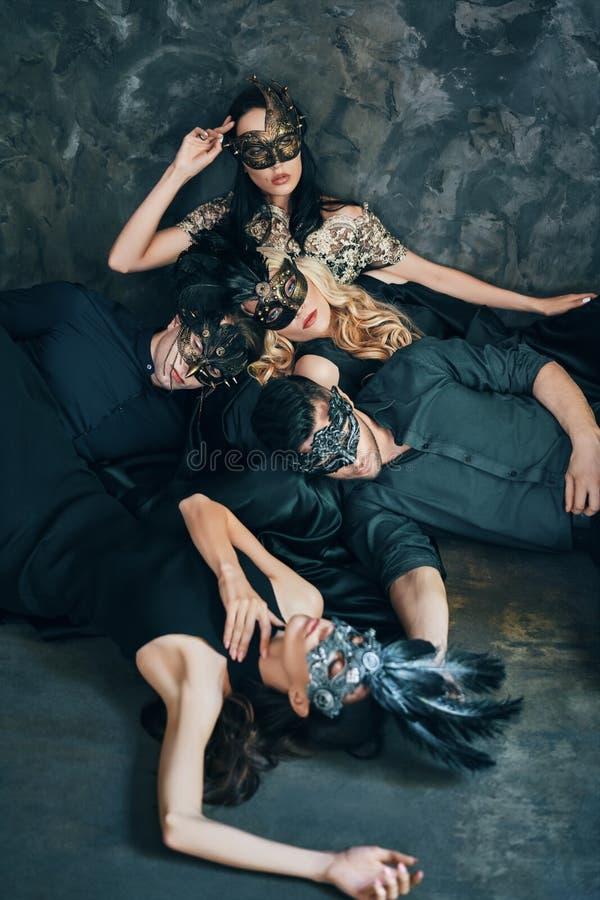 Группа в составе друзья в маске масленицы masquerade сидя на поле ослабляет после партии стоковое фото