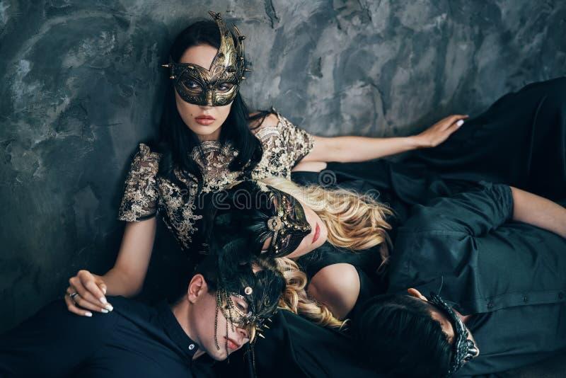 Группа в составе друзья в маске масленицы masquerade сидя на поле ослабляет после партии стоковые фото