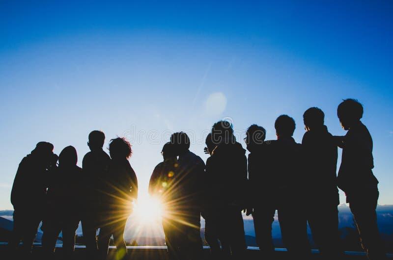 Группа в составе друзья наблюдая восход солнца стоковое фото rf