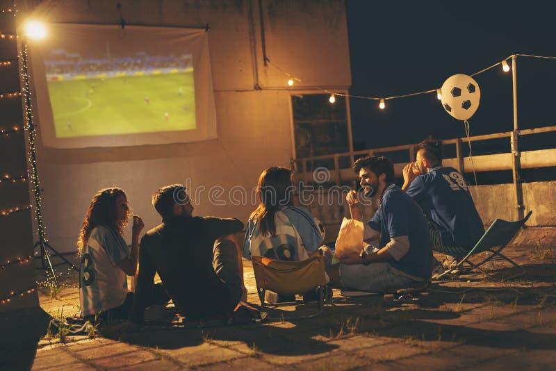 Группа в составе друзья наблюдая футбол на крыше здания стоковая фотография rf