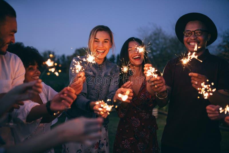 Группа в составе друзья наслаждаясь вне с бенгальскими огнями стоковые фото