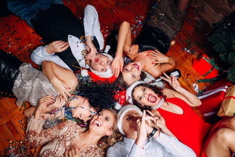 Группа в составе друзья на клубе имея потеху и лежа на поле Партия ` s Нового Года стоковые изображения rf