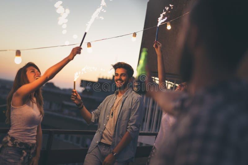 Группа в составе друзья на партии крыши стоковое изображение