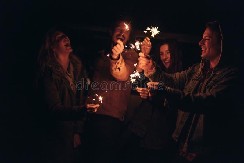 Группа в составе друзья освещая sparkles огня стоковые фото