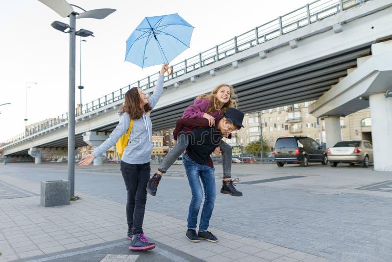 Группа в составе друзья подростков имея потеху в городе, смеясь детей с зонтиком Городской предназначенный для подростков образ ж стоковые фотографии rf