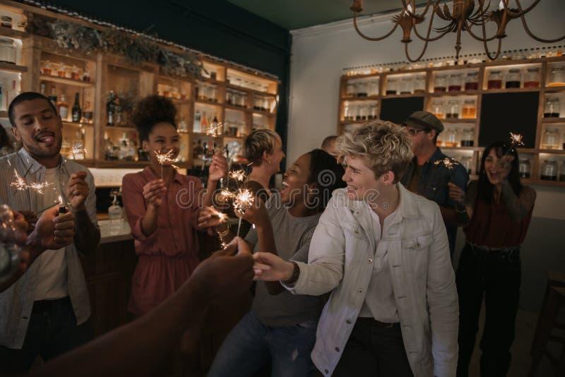 Группа в составе друзья празднуя с бенгальскими огнями в баре стоковое фото rf