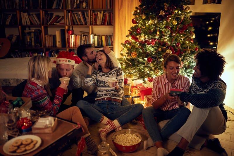 Группа в составе друзья сидя рядом с рождественской елкой, ел печенья рождества, выпивая какао и потеху иметь стоковое изображение