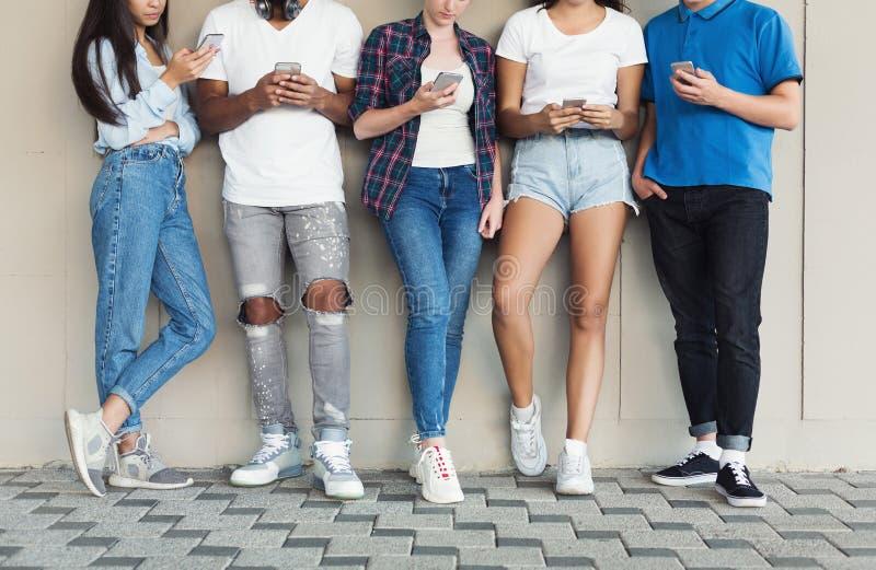 Группа в составе друзья multiculture используя смартфон на городской предпосылке стоковое фото