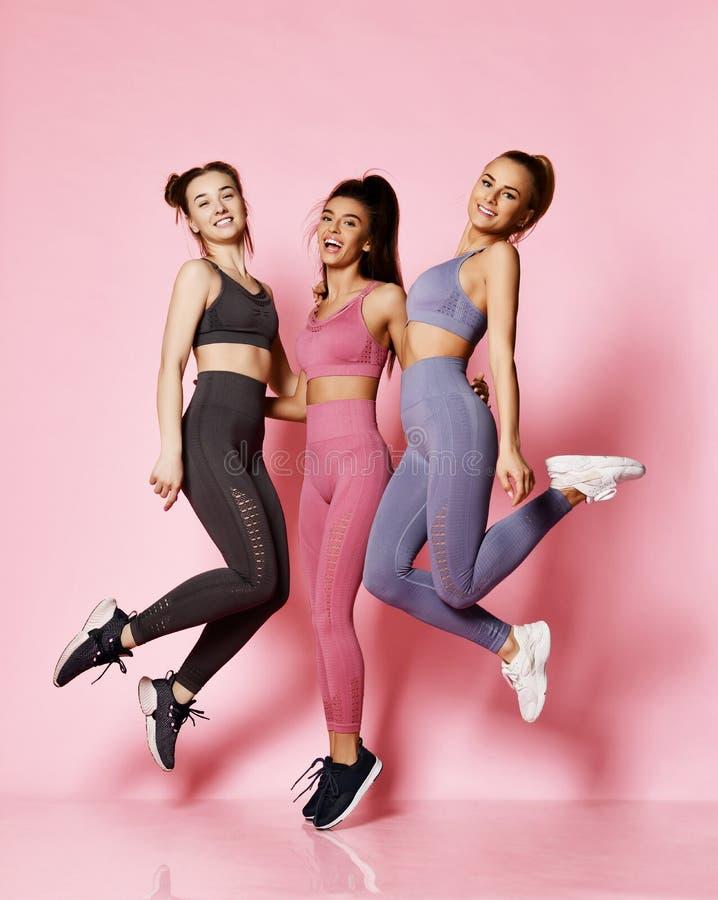 Группа в составе 3 друз девушек спорта международных в современных спорт носит иметь потеху Выполняющ скачки и тренировки совмест стоковые фото