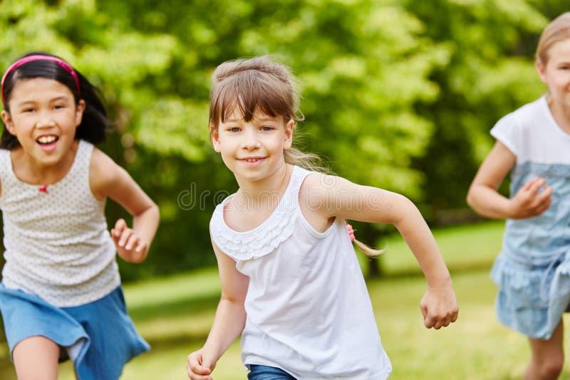 Группа в составе дети бежать в парке стоковое фото