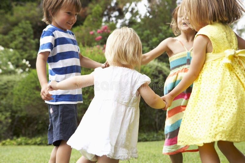 Группа в составе дети играя Outdoors совместно стоковые изображения