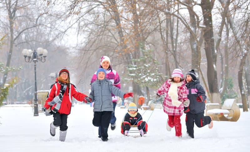 Группа в составе дети и мать играя на снеге в зимнем времени стоковые изображения rf