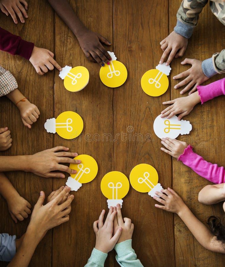Группа в составе дети коллективно обсуждать и деля идеи с электрической лампочкой стоковое фото