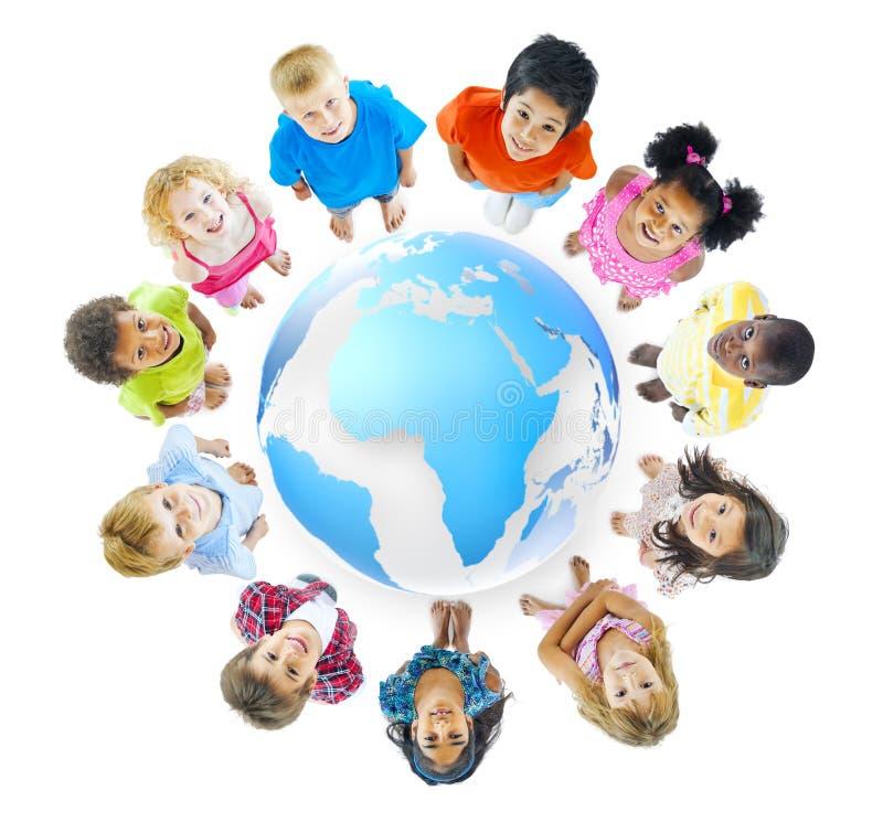 Группа в составе дети стоя вокруг карты мира стоковая фотография rf