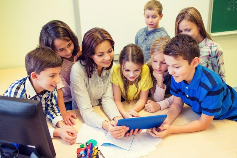 Группа в составе дети с ПК учителя и таблетки на школе стоковые изображения