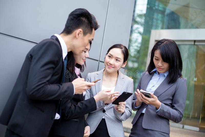 Группа в составе дело обсуждает на мобильном телефоне стоковое фото