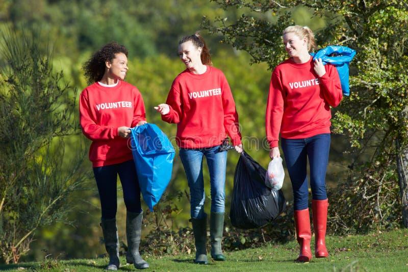 Группа в составе женские волонтеры собирая сор стоковые изображения