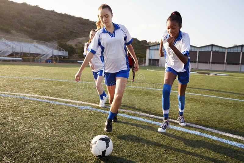 Группа в составе женские студенты средней школы играя в футбольной команде стоковые изображения