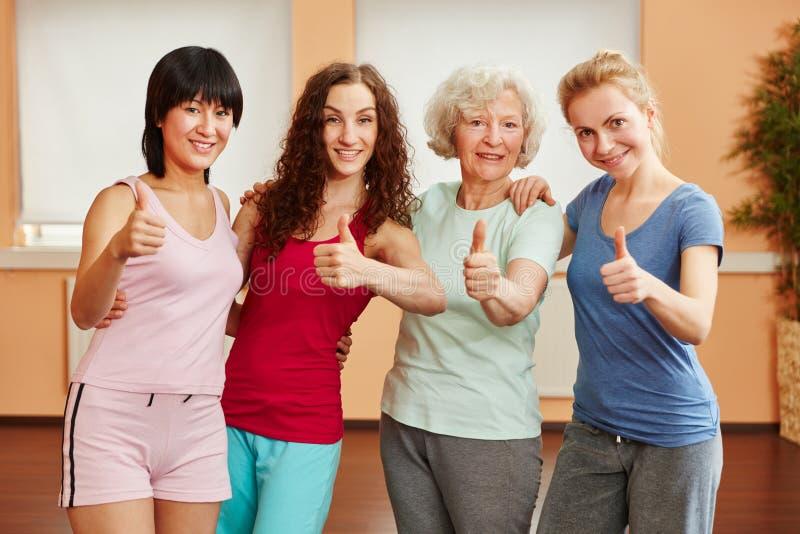 Группа в составе женщины держа большие пальцы руки вверх стоковые фото