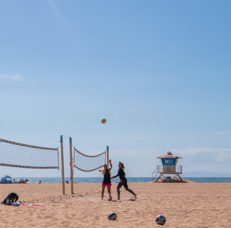 Группа в составе женщины играя волейбол на пляже на Huntington Beach, Калифорния стоковые фотографии rf