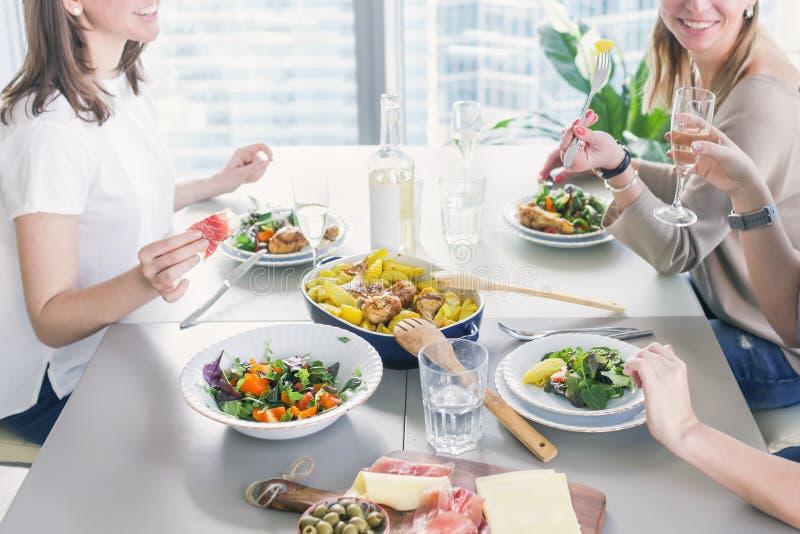 Группа в составе женщины имея обедающий Счастливое womwn наслаждаясь обедающим совместно стоковые изображения rf