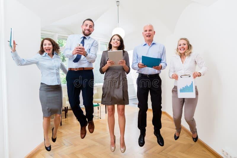 Группа в составе женщины и люди в скакать офиса стоковое изображение rf