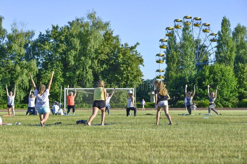 Группа в составе женщины различных возрастов выполняет гимнастические тренировки на стадионе города, России, регионе Курск, Zhele стоковые фотографии rf