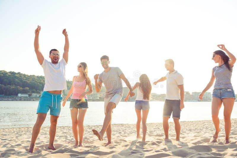 Группа в составе жизнерадостные люди имея партию и танцевать пляжа стоковое фото rf