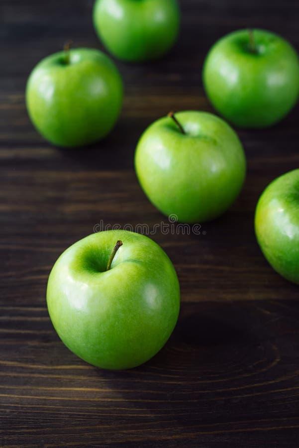 Группа в составе зеленые яблоки на коричневой деревянной предпосылке иллюстрация штока