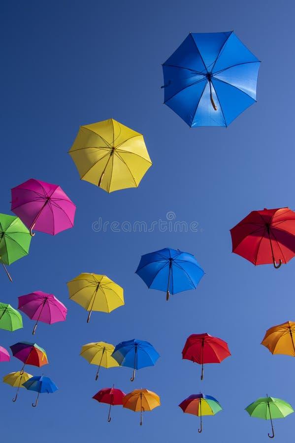 Группа в составе зонтики летания изолированные на голубой предпосылке, подготавливает для дождя, предпосылки обоев, ярких различн стоковая фотография rf