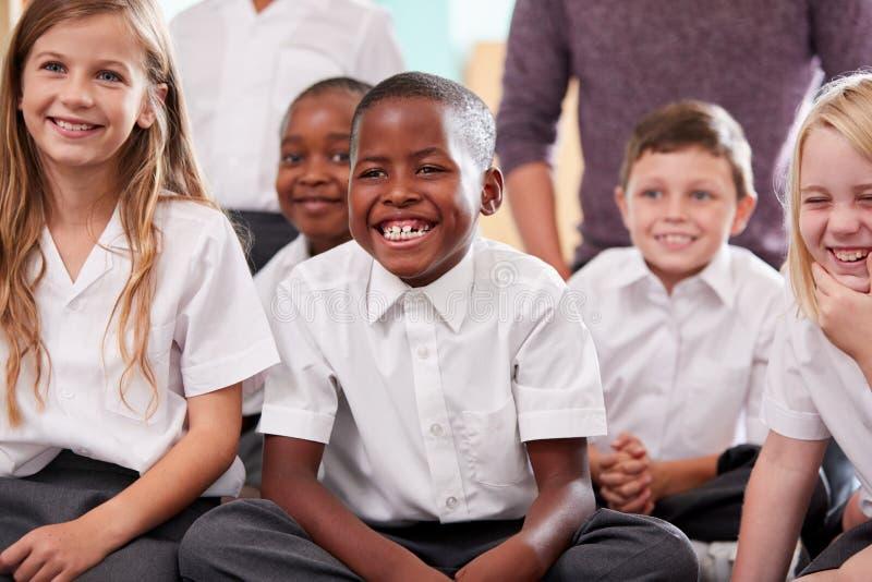 Группа в составе зрачки начальной школы нося равномерное усаживание на поле слушая учителя стоковая фотография