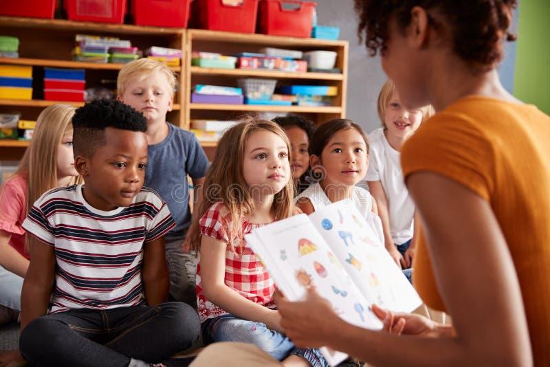 Группа в составе зрачки начальной школы сидя на поле слушая рассказ чтения учительницы стоковое фото rf