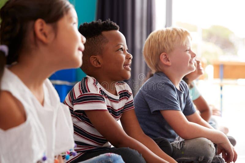 Группа в составе зрачки начальной школы сидя на поле слушая учителя стоковое фото