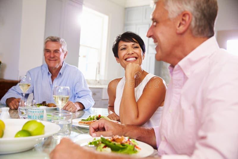 Группа в составе зрелые друзья наслаждаясь едой дома совместно стоковое фото