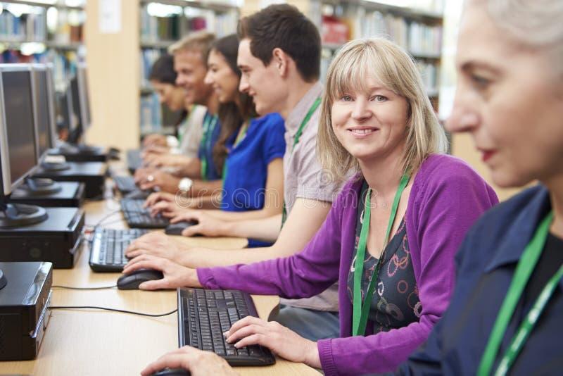 Группа в составе зрелые студенты работая на компьютерах стоковое фото rf