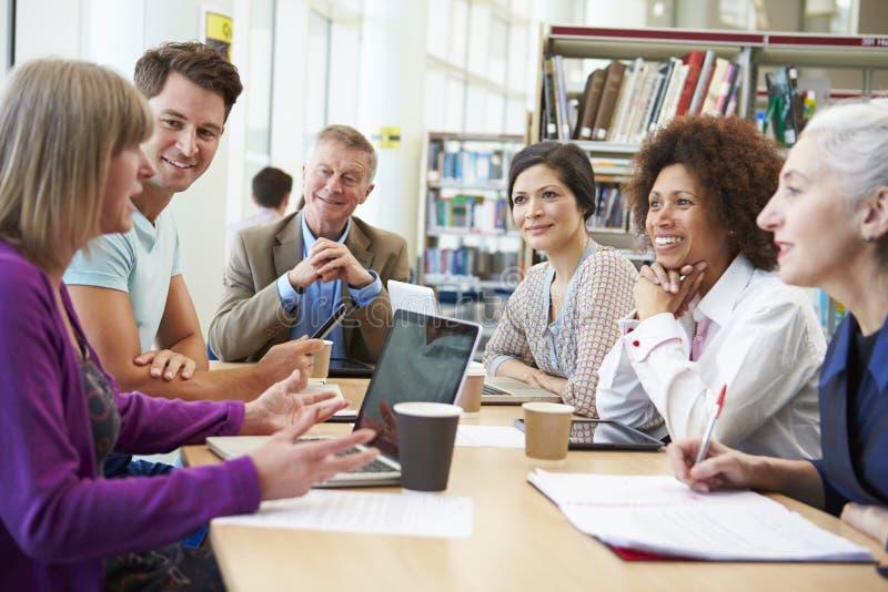 Группа в составе зрелые студенты сотрудничая на проекте в библиотеке стоковые изображения rf