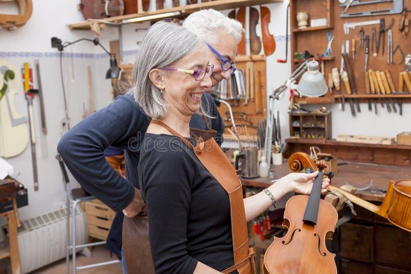 Группа в составе зрелый создатель скрипки в представлении стоковое фото