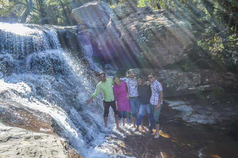 Группа в составе индийские друзья имея потеху в водопаде в королевском натальном национальном парке Южной Африке стоковая фотография