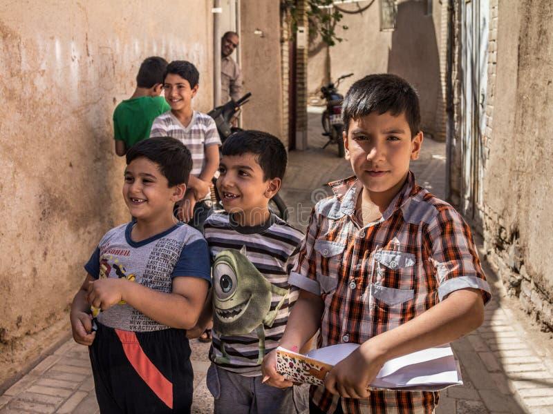 Группа в составе иранские студенты зрачков, мальчиков, основных и средней школы, положение и играть, одно держа тетрадь исследова стоковая фотография