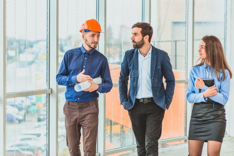 Группа в составе красивые деловые партнеры в подныривании Обсуждающ план, архитектор стоит в кассире стоковые фото